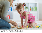 Купить «Kid girl playing with developmental toys at home or kindergarten», фото № 28053561, снято 19 сентября 2018 г. (c) Оксана Кузьмина / Фотобанк Лори