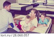 Купить «Happy parents with two sons testing mattress in store», фото № 28060057, снято 26 июня 2017 г. (c) Яков Филимонов / Фотобанк Лори