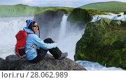 Купить «Girl tourist sitting on a rock enjoying the beautiful view of Godafoss waterfall in Iceland», видеоролик № 28062989, снято 17 сентября 2017 г. (c) Алексей Кузнецов / Фотобанк Лори