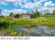 Купить «Старый деревянный разрушающийся дом у пруда», фото № 28063265, снято 10 августа 2017 г. (c) Pukhov K / Фотобанк Лори