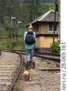 Купить «Female backpacker walking on railroad track followed by her dog.», фото № 28069161, снято 23 июля 2019 г. (c) Matej Kastelic / Фотобанк Лори