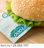 Купить «Burger with one thousand ruble bill», фото № 28069197, снято 11 февраля 2018 г. (c) Георгий Дзюра / Фотобанк Лори