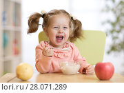 Купить «cheerful baby child eating food itself with a spoon», фото № 28071289, снято 30 мая 2020 г. (c) Оксана Кузьмина / Фотобанк Лори