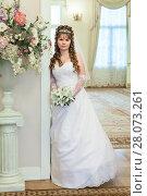 Купить «Beautiful young bride standing indoor with wedding bouquet, full-length», фото № 28073261, снято 26 февраля 2012 г. (c) Кекяляйнен Андрей / Фотобанк Лори
