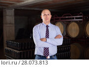 Confident succesful man winemaker posing in own winery vault. Стоковое фото, фотограф Яков Филимонов / Фотобанк Лори