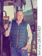 Купить «Confident male owner of vineyard posing near tractor outdoors in sunny day», фото № 28073821, снято 22 января 2018 г. (c) Яков Филимонов / Фотобанк Лори