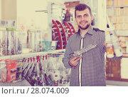 cheerful male customer examining various glue tubes in store. Стоковое фото, фотограф Яков Филимонов / Фотобанк Лори