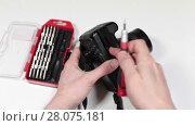 Купить «Снятие аккумулятора из фотоаппарата и раскручивание крышки корпуса для ремонта», видеоролик № 28075181, снято 26 февраля 2018 г. (c) Кекяляйнен Андрей / Фотобанк Лори