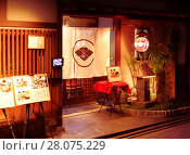 Купить «Mitoko, traditional Japanese Kaiseki restaurant lit by the lights of lanterns at night with a Noren curtain in the entrance door and menus displayed outside...», фото № 28075229, снято 19 ноября 2017 г. (c) age Fotostock / Фотобанк Лори