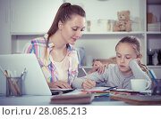 Купить «Woman and smiling girl writting with pen», фото № 28085213, снято 29 апреля 2017 г. (c) Яков Филимонов / Фотобанк Лори