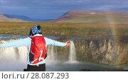 Купить «Girl tourist enjoys the view of the Godafoss waterfall with a rainbow in Iceland», видеоролик № 28087293, снято 2 ноября 2017 г. (c) Алексей Кузнецов / Фотобанк Лори