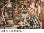 Купить «male worker sewing stitches on belt in leather workshop», фото № 28088097, снято 22 марта 2019 г. (c) Яков Филимонов / Фотобанк Лори