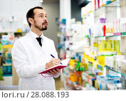 Купить «Male pharmacist checking assortment of drugs», фото № 28088193, снято 14 декабря 2016 г. (c) Яков Филимонов / Фотобанк Лори