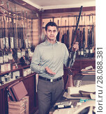 Купить «Handsome adult male owner of hunting shop offering rifle», фото № 28088381, снято 11 декабря 2017 г. (c) Яков Филимонов / Фотобанк Лори
