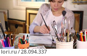 Middle age woman painting with watercolors in art studio with brushes in foreground. Стоковое видео, видеограф Алексей Кузнецов / Фотобанк Лори
