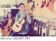 Купить «teenage customers deciding on suitable acoustic guitar in guitar shop», фото № 28097781, снято 14 февраля 2017 г. (c) Яков Филимонов / Фотобанк Лори