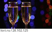 Купить «Two glasses with champagne appear from blur on black background with flashing lights», видеоролик № 28102125, снято 12 февраля 2016 г. (c) Алексей Кузнецов / Фотобанк Лори