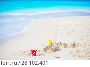 Купить «Sandcastle at white tropical beach with plastic kids toys», фото № 28102401, снято 5 января 2018 г. (c) Дмитрий Травников / Фотобанк Лори