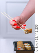 Купить «The female hand with magnificent manicure takes sushi from a black plate by means of wooden sticks», фото № 28112233, снято 4 февраля 2018 г. (c) Anatoly Timofeev / Фотобанк Лори