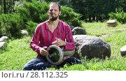 Купить «Young man playing the drum in a city park on a sunny summer day. Audio included», видеоролик № 28112325, снято 3 августа 2015 г. (c) Алексей Кузнецов / Фотобанк Лори