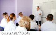 Male medical student answering near whiteboard in front of teacher and group of students in auditorium. Стоковое видео, видеограф Яков Филимонов / Фотобанк Лори