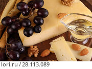 Купить «Сыр грюйер на деревянном столе с виноградом, орехами и оливковым маслом», фото № 28113089, снято 3 марта 2018 г. (c) Марина Володько / Фотобанк Лори