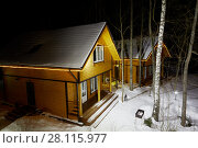 Купить «Illuminated wooden houses on winter evening among trees», фото № 28115977, снято 3 февраля 2017 г. (c) Losevsky Pavel / Фотобанк Лори