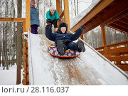 Купить «Three children play and ride snow tube on wooden slide covered with snow on winter day», фото № 28116037, снято 4 февраля 2017 г. (c) Losevsky Pavel / Фотобанк Лори