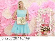 Купить «Pretty young woman in dress poses with gift near wall with big flowers in studio», фото № 28116169, снято 31 октября 2016 г. (c) Losevsky Pavel / Фотобанк Лори