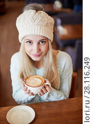Купить «Young smiling blonde woman in knitted hat with fur pompom sits in cafeteria at table with cup of coffee in hands», фото № 28116249, снято 1 ноября 2016 г. (c) Losevsky Pavel / Фотобанк Лори