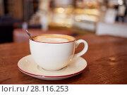 Купить «Cup of coffee on wooden table in cafeteria», фото № 28116253, снято 1 ноября 2016 г. (c) Losevsky Pavel / Фотобанк Лори