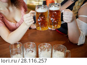 Купить «Two women clang glass mugs with beer above table, no faces», фото № 28116257, снято 23 марта 2019 г. (c) Losevsky Pavel / Фотобанк Лори