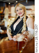 Купить «Smiling blonde woman stands holding spikelet in hand and leaning elbow on bar counter with beer mugs in cafe», фото № 28116297, снято 1 ноября 2016 г. (c) Losevsky Pavel / Фотобанк Лори