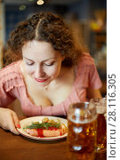 Купить «Smiling woman with curly hair sniffs fried sausages with sprig of dill on plate in cafe», фото № 28116305, снято 1 ноября 2016 г. (c) Losevsky Pavel / Фотобанк Лори