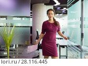Купить «Beautiful woman in dress holds pen, paper and smiles in modern office», фото № 28116445, снято 20 ноября 2016 г. (c) Losevsky Pavel / Фотобанк Лори