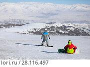Купить «Two snowboarders are on mountain in ski resort, back view, factory far away», фото № 28116497, снято 7 января 2017 г. (c) Losevsky Pavel / Фотобанк Лори