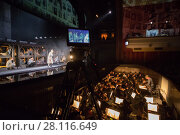 Купить «MOSCOW - JAN 25, 2017: Shooting camera, prisoners on stage and orchestra pit at Passenger performance in Moscow Theater New Opera, focus on camera», фото № 28116649, снято 25 января 2017 г. (c) Losevsky Pavel / Фотобанк Лори