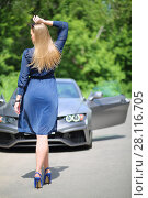 Купить «Woman with long hair in a blue dress with arm raised in front of a silver sports car and green foliage, view from the back», фото № 28116705, снято 19 июня 2016 г. (c) Losevsky Pavel / Фотобанк Лори