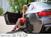 Купить «Plump blonde with long hair in a red dress sitting in the sport car with an open door in front of green tree», фото № 28116729, снято 19 июня 2016 г. (c) Losevsky Pavel / Фотобанк Лори