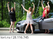Купить «MOSCOW - JUN 19, 2016: Three happy beautiful girls (with model releases) with long hair cheerfully laughing and fooling near the sport car in front of green foliage», фото № 28116745, снято 19 июня 2016 г. (c) Losevsky Pavel / Фотобанк Лори