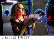 Купить «MOSCOW - DEC 13, 2014: Woman with curly hair (with model release) in a special vest with a laser-automat in laser tag at the shopping center Capitol Vernadsky», фото № 28116789, снято 13 декабря 2014 г. (c) Losevsky Pavel / Фотобанк Лори
