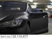 Купить «Modern black car with open door stands at underground parking, focus on mirror bracket», фото № 28116877, снято 11 ноября 2015 г. (c) Losevsky Pavel / Фотобанк Лори