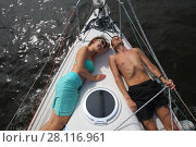 Купить «Man and woman lie on snout of yacht on river at summer sunny day, top view», фото № 28116961, снято 19 августа 2016 г. (c) Losevsky Pavel / Фотобанк Лори