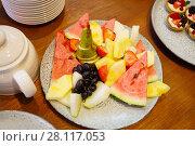 Купить «Pieces of fruit on plate, watermelon, grapes, pineapple, melon, pear, strawberry», фото № 28117053, снято 20 октября 2016 г. (c) Losevsky Pavel / Фотобанк Лори