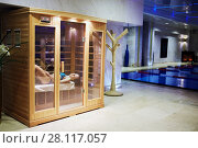 MOSCOW, RUSSIA - NOV 14, 2015: Woman in swimsuit lies on bench in infrared sauna cabin behind glass doors in recreational area in Radisson Royal Ukraine hotel, one of seven Stalin skyscrapers. Редакционное фото, фотограф Losevsky Pavel / Фотобанк Лори