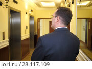 Купить «Man in a business suit standing in the hallway between the elevator and mirrors in the luxury apartment building, back view», фото № 28117109, снято 21 февраля 2016 г. (c) Losevsky Pavel / Фотобанк Лори