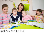 Купить «Little four children and young woman are sitting at the table with books», фото № 28117133, снято 28 апреля 2015 г. (c) Losevsky Pavel / Фотобанк Лори