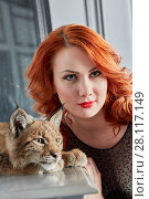 Купить «Closeup face of red-haired young woman and muzzle of lynx cub», фото № 28117149, снято 14 ноября 2015 г. (c) Losevsky Pavel / Фотобанк Лори