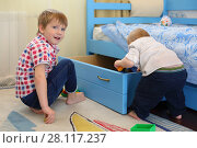 Купить «Two little brothers play toys near bed with big drawer in room», фото № 28117237, снято 7 мая 2016 г. (c) Losevsky Pavel / Фотобанк Лори