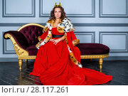 Купить «Woman in red dress, cloak and with crown on head sits on couch in room», фото № 28117261, снято 14 ноября 2015 г. (c) Losevsky Pavel / Фотобанк Лори